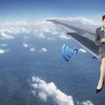 Business Woman Sitting On Airplane Wing Texting